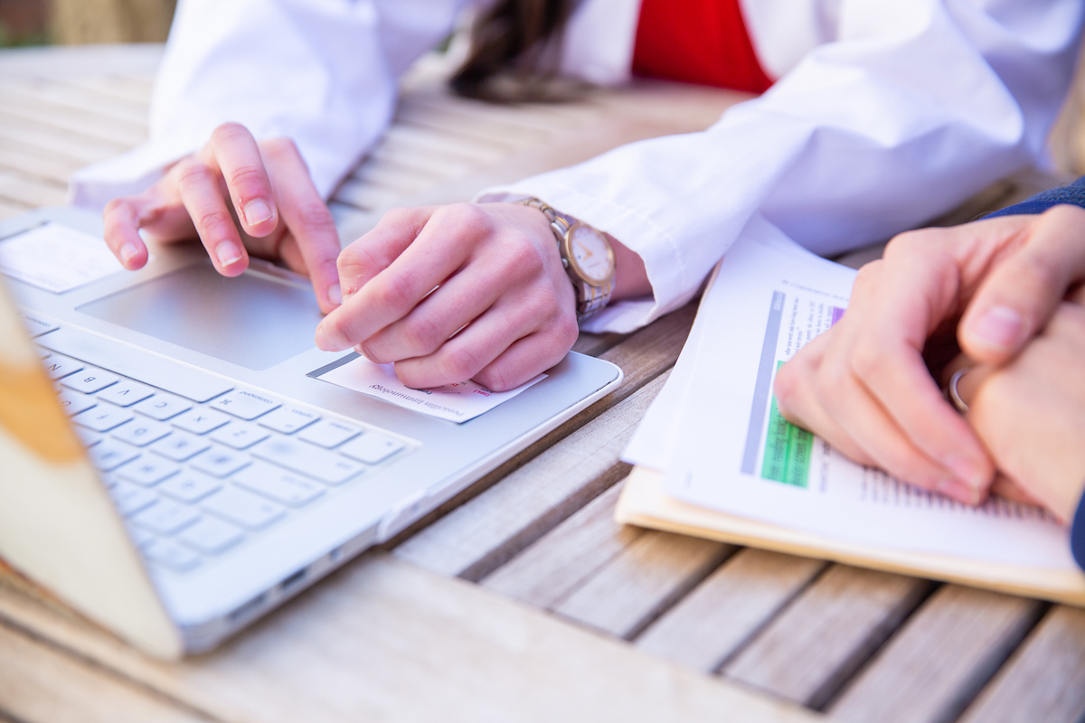 Hands of a medical student using a laptop and hands of a person holding paperwork